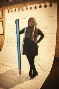 Photo shows a young woman with a giant pencil. She stands on what appears to be a sheet from a notebook, enlarged 25 times. Notes on the page refer to 'scale'.